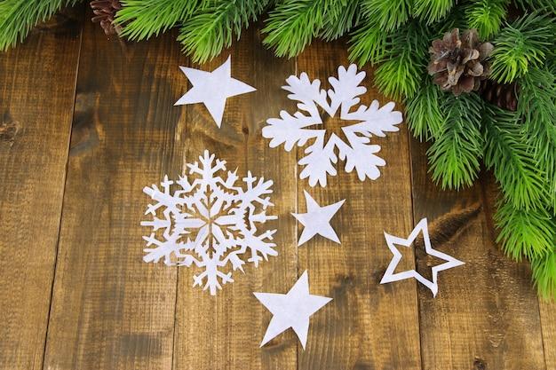 Красивые бумажные снежинки с еловой веткой на деревянных фоне