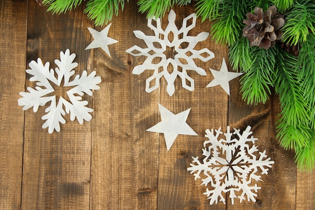 Beautiful paper snowflakes with fir branch on wooden table