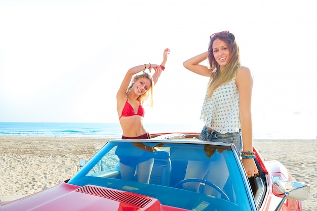 Beautiful party friend girls dancing in a car on the beach