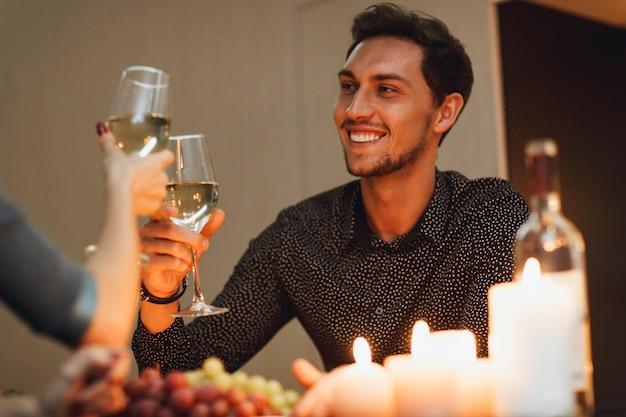 家でロマンチックなキャンドルライトディナーを楽しんだり、ワインを飲んだり、乾杯したりする美しい情熱的なカップル