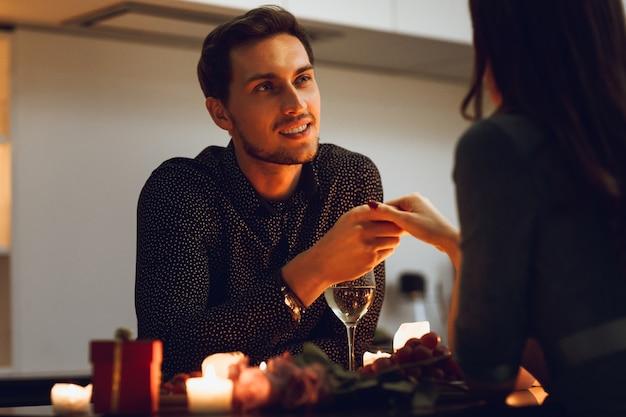 家でロマンチックなキャンドルライトディナーを持っている美しい情熱的なカップル、手にキスする男