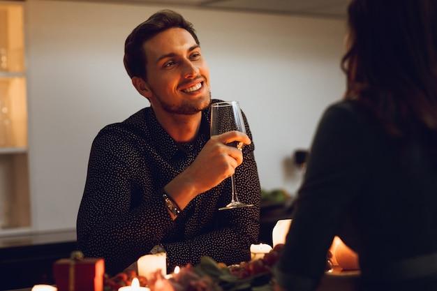 家でロマンチックなキャンドルライトディナーを持っている美しい情熱的なカップル