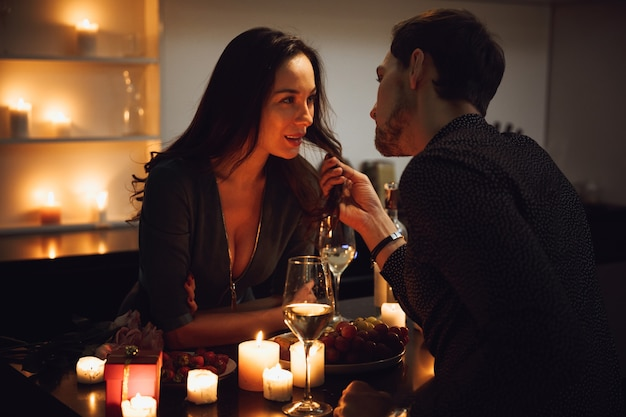 Beautiful passionate couple having a romantic candlelight dinner at home, drinking wine, toasting, embracing