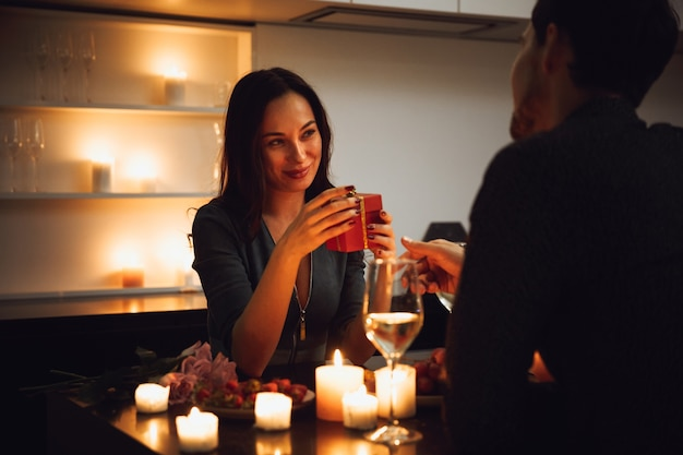Beautiful passionate couple having a romantic candlelight dinner at home, drinking wine, woman getting a gift box