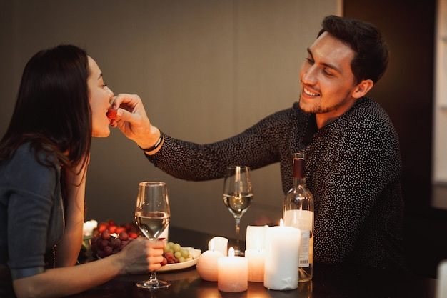 Beautiful passionate couple having a romantic candlelight dinner at home, feeding each other