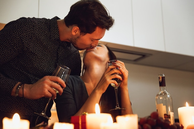 Beautiful passionate couple having a romantic candlelight dinner at home, kissing