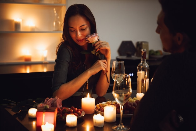 Beautiful passionate couple having a romantic candlelight dinner at home, woman smelling a flower