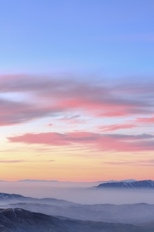 Beautiful pastel sunset above rocky mountains covered in the cloud