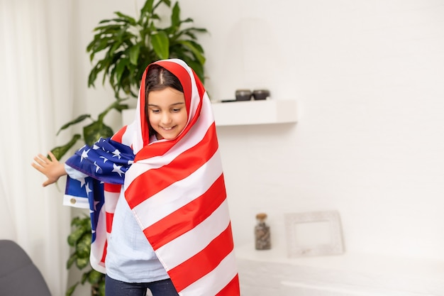 미국 국기와 함께 아름 다운 애국 어린 소녀는 그녀의 뻗은 손에 개최.