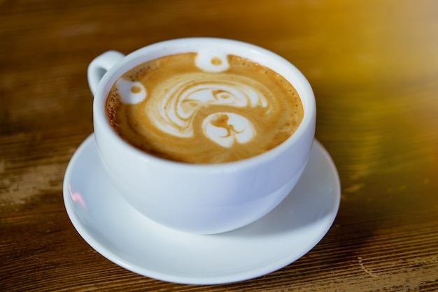 Beautiful pattern in the form of bear in a white cup with a latte maded in the restaurant.