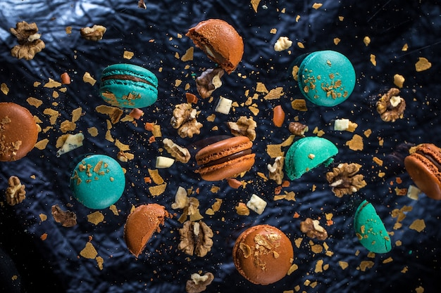 Beautiful pattern of macaroon with walnuts lie on the glass on the blue background