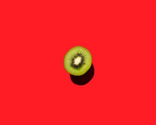 赤い背景の上のキウイフルーツの美しい模様。スペースをコピーします。