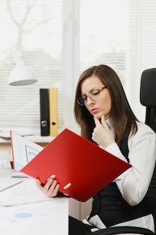 Beautiful pensive brown-hair business woman in black and white suit and glasses sitting at the desk with red folder, mobile phone and cup of coffee, working at computer with documents in light office.