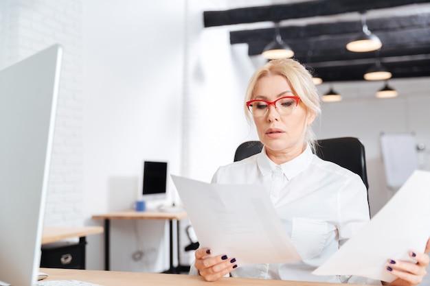 オフィスで論文を読んで美しい物思いにふける成熟した実業家