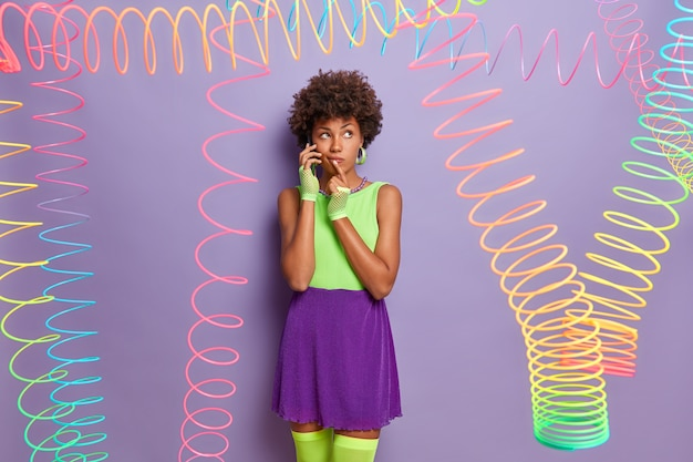 Beautiful pensive woman in colorful clothing, wears sport gloves and stockings, talks via mobile phone