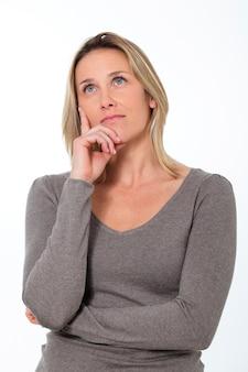 Beautiful pensive woman in studio looking up