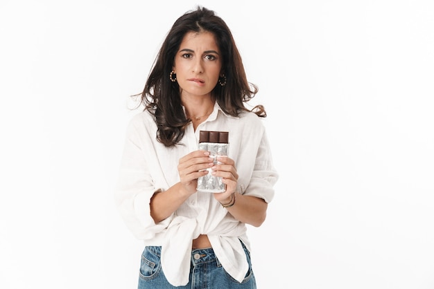 Beautiful pensive young brunette woman wearing casual clothing standing isolated over white wall, holding chocolate plate