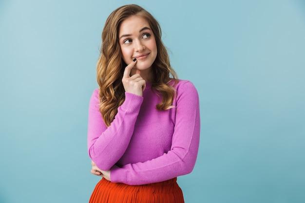 Красивая задумчивая молодая девушка в повседневной одежде, стоящая изолированно над синей стеной