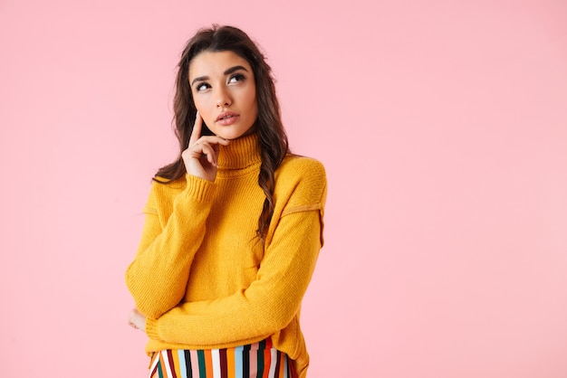 Beautiful pensive young woman wearing colorful clothes standing isolated over pink