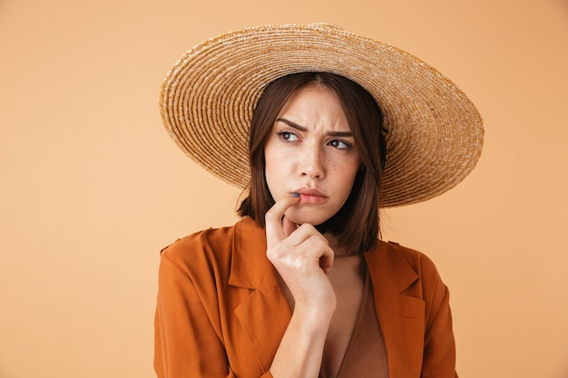 Beautiful pensive young woman wearing straw hat and summer outfit standing isolated over beige wall