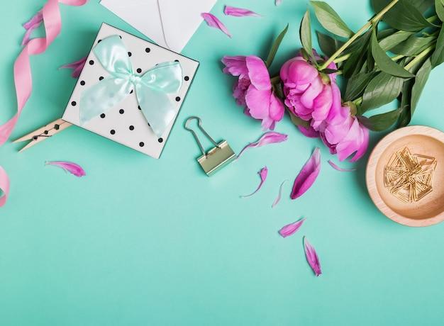 Красивые пионы и подарочная коробка на модном фоне мятного цвета, вид сверху