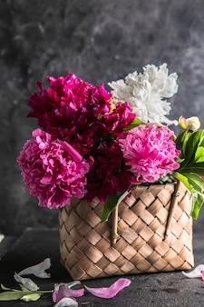 Beautiful peonies in wicker basket on wooden table