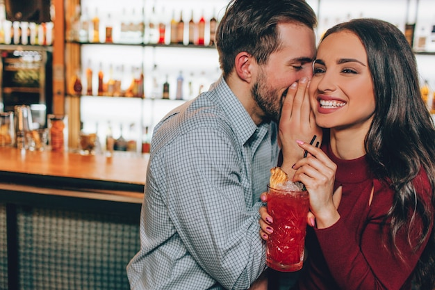 Beautiful people are sitting very close to each other in bar. he is whispering something in her ear while she is smiling and laughing. also girl is holding a glass of red cocktail.