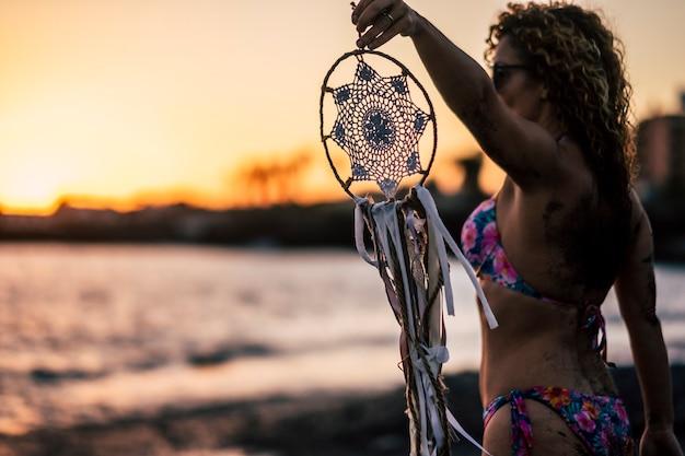 夏休み休暇の自由な気持ちで夕日を楽しむビーチで屋外の白いドリームキャッチャーを保持しているビキニを持つ美しい人々の女性
