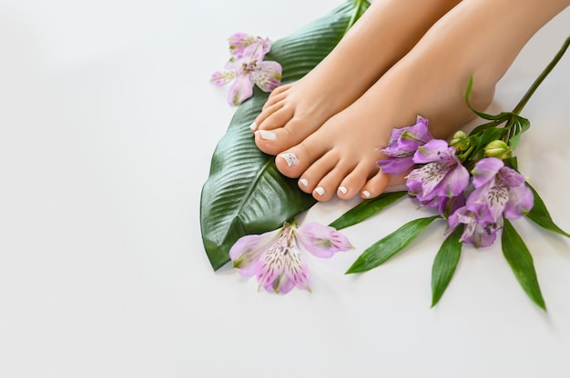Beautiful perfect female feet top view with tropical flowers and green palm leaf