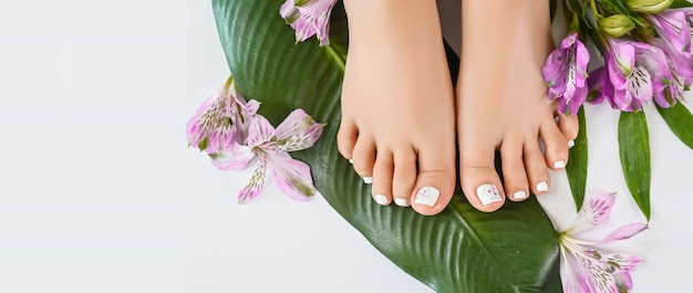 Beautiful perfect female skin legs feet top view with tropical flowers and green palm leaf