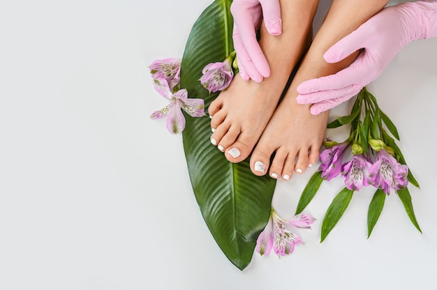 Beautiful perfect skin female legs feet top view with tropical flowers and green palm leaf