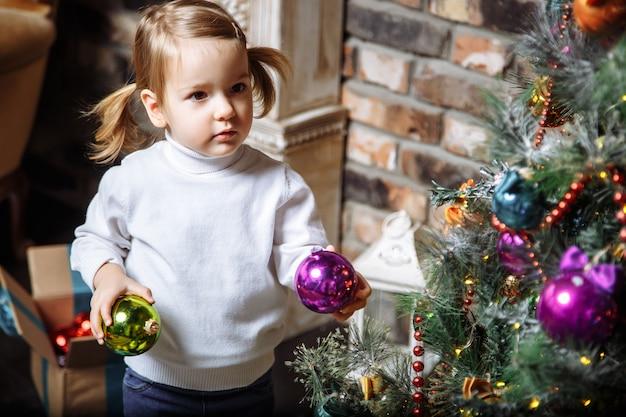 自宅でクリスマスツリーを飾るかわいい女の子の美しい写真