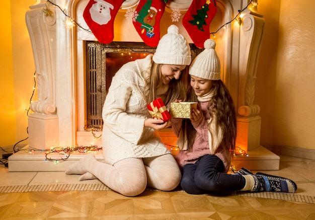 クリスマス プレゼントと暖炉のそばに座っている母と娘の美しい写真