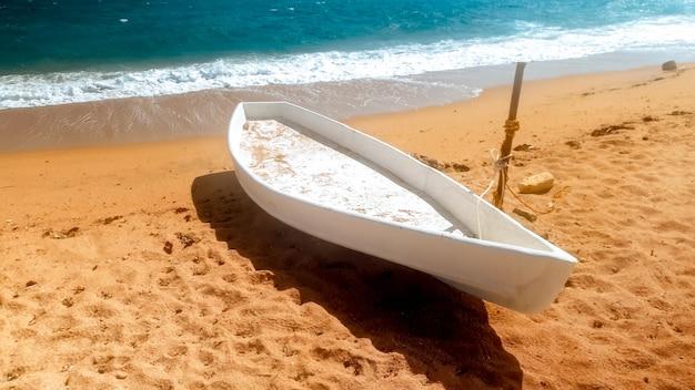 바다에 누워 오래 된 흰색 나무 보트의 아름 다운 사진. 해변에서 fesherman 보트
