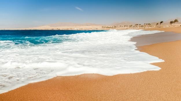 Красивое фото морских волн, катящихся на морском пляже. идеальный фон для летнего отпуска