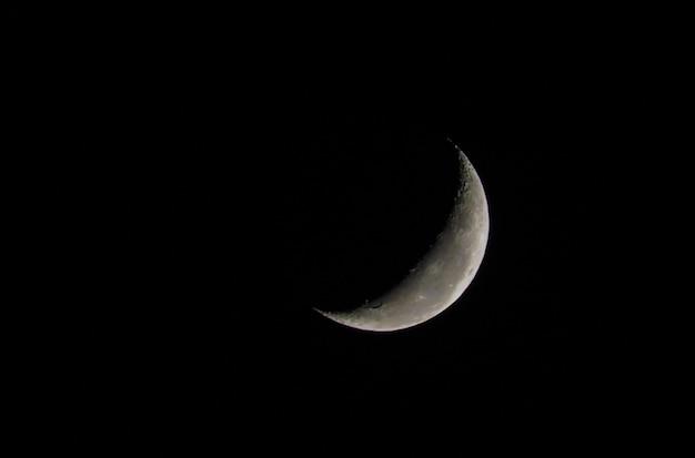 쇠퇴하는 달의 아름다운 사진은 어두운 하늘과 가까이