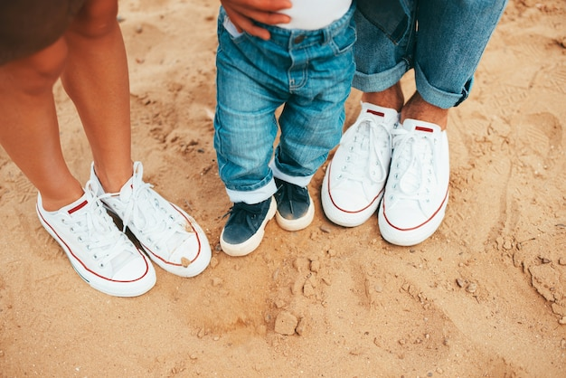 Beautiful photo of three pairs of shoes mom, dad and baby son on beach