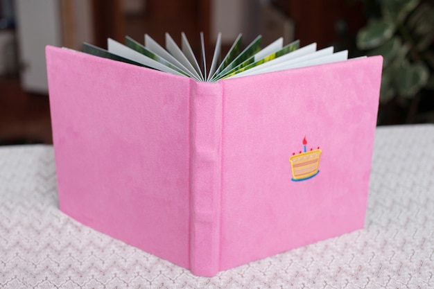 Beautiful photobook in light pink textile cover.