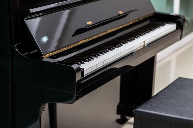 Beautiful piano next to a stool