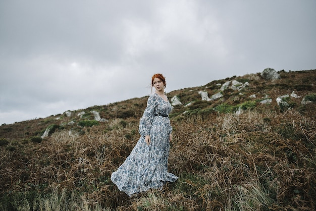 Beautiful picture of a ginger female with a pure white skin in an attractive light blue gown