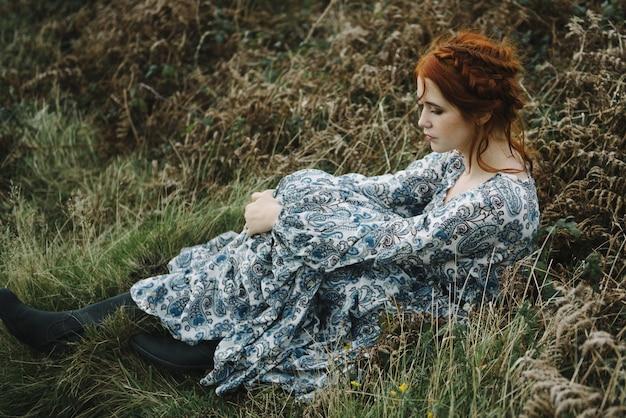 매력적인 하늘색 가운에 순수한 흰색 피부를 가진 생강 여성의 아름다운 그림