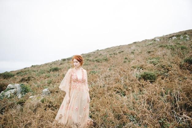매력적인 밝은 분홍색 가운에 순수한 흰색 피부를 가진 생강 여성의 아름다운 그림
