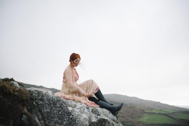 ピンクのガウンで真っ白な肌を持つ生姜の女性の美しい写真