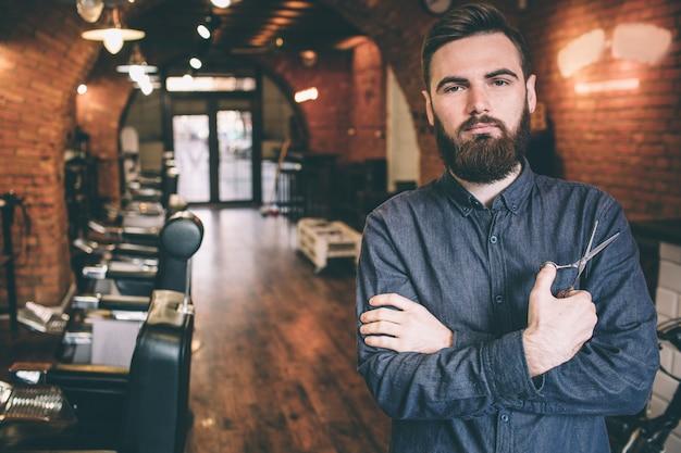 Красивое изображение красивого парня стоит в парикмахерской и keepinh его руки пересеклись. он держит ножницы в правой руке.