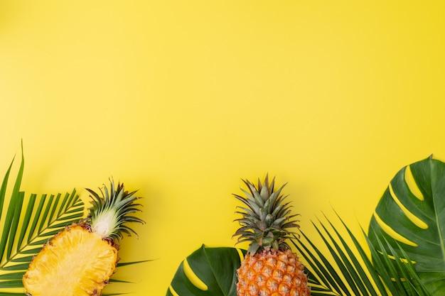 トロピカルパームモンステラの葉の美しいパイナップルは、明るいパステルイエローの背景、上面図、フラットレイ、夏の果物の上の頭上に分離されました。