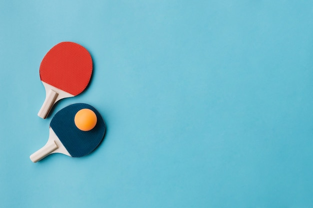 Beautiful ping pong rackets with ball over blue underground