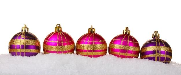 Красивые розовые и фиолетовые елочные шары в снегу, изолированные на белом