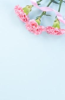 어머니의 날 꽃 개념에 대 한 옅은 파란색 테이블 배경에 아름 다운 핑크 카네이션.