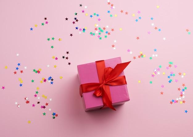 Красивая розовая закрытая коробочка с большим бантом с разноцветными блестками