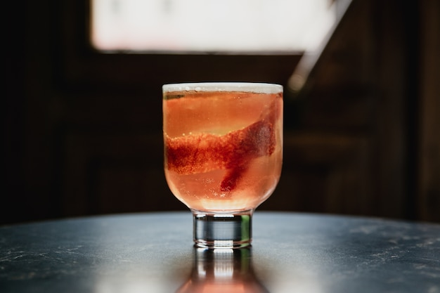 A beautiful pink cocktail with a big ice cube in a lowball glass, garnished with blood orange zest